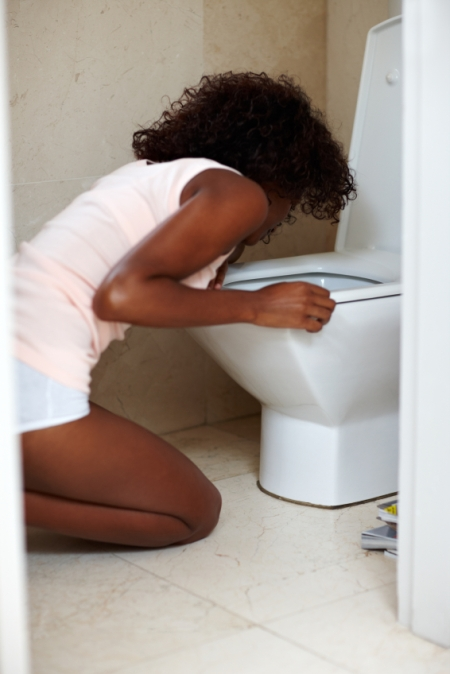 Bulimic young african woman forcing herself to vomit